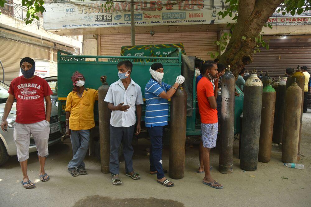 كارثة إنسانية كبرى - تسجيل أرقام قياسية لحالات الإصابة بمرض كوفيد-19، كورونا، أشخاص يفقون في طابور في انتظار ملء أنابيب الأكسجين في نيودلهي، الهند 28 أبريل 2021