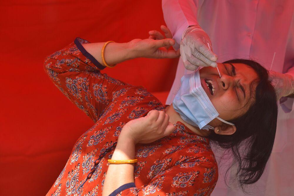 كارثة إنسانية كبرى - تسجيل أرقام قياسية لحالات الإصابة بمرض كوفيد-19، امرأة شابة تلجأ لاختبار كورونا في نيودلهي، الهند 28 أبريل 2021