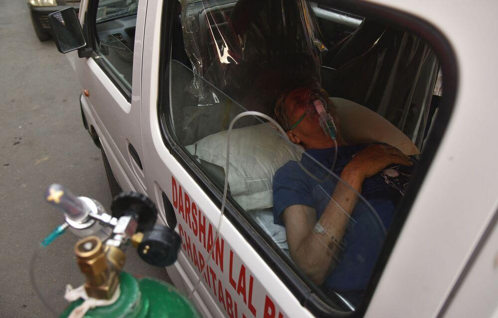 كارثة إنسانية كبرى - تسجيل أرقام قياسية لحالات الإصابة بمرض كوفيد-19،رجل داخل سيارة إسعاف ينتظر دوره لتلقي جرعة الأكسجين و الدعم الطبي في أحد معابد غورودفار في نيودلهي، الهند 28 أبريل 2021