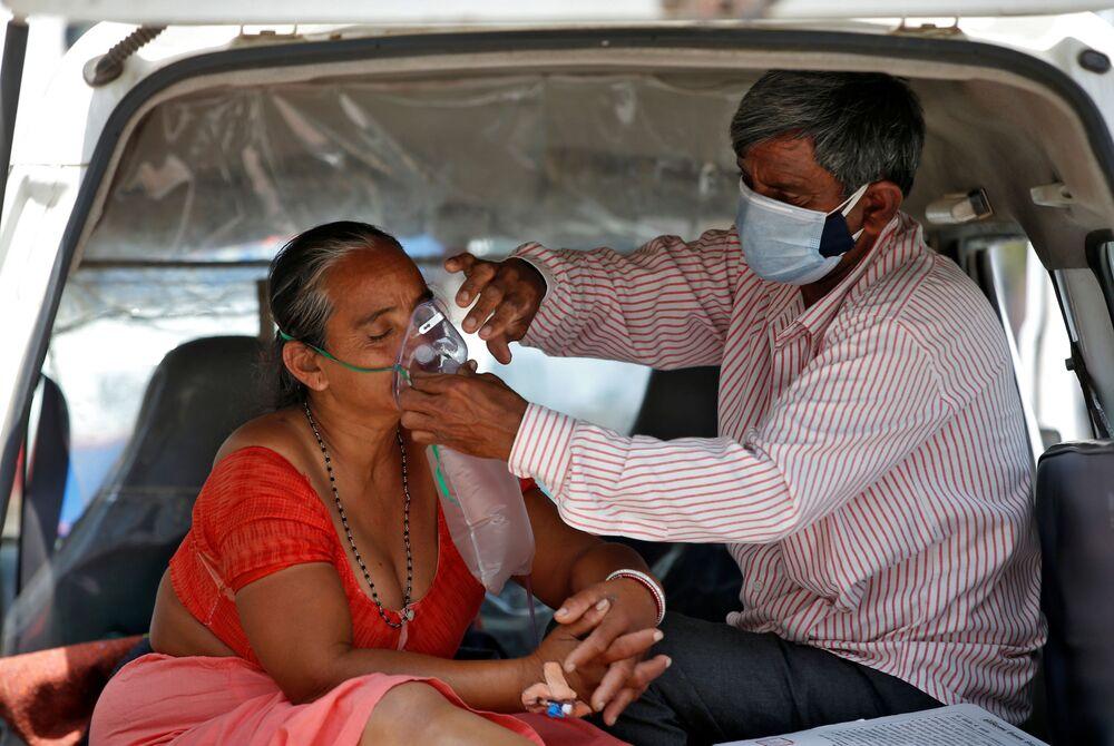 كارثة إنسانية كبرى - تسجيل أرقام قياسية لحالات الإصابة بمرض كوفيد-19، زوج يهتم بتعديل قناع الأكسجين لزوجته داخل سيارة للدخول إلى مشفى لتلقي العلاج في أحمدآباد، الهند 28 أبريل 2021