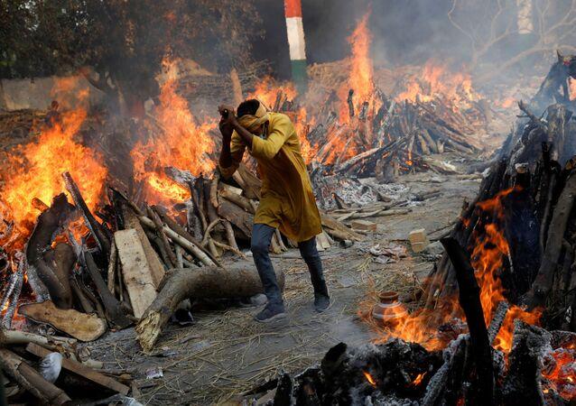 رجل يسير بجوار موقع لحرق جثث ضحايا كورونا، إثر تسجيل أرقام قياسية لحالات الإصابة بمرض كوفيد-19 وعدم توفر ثلاجات ومقابر تكفي الأموات، في نيودلهي، الهند 26 أبريل 2021