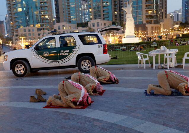أفراد من شرطة الإمارات يصلون بعد الإفطار خارج مبنى دبي مول ، الإمارات العربية المتحدة، 23 أبريل 2021