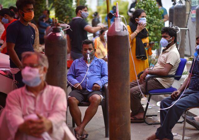 أشخاص يعانون من نقص الأكسجين وبنتظرون لتلقي الدعم في أحد معابد غورودفار في نيودلهي، الهند 28 أبريل 2021