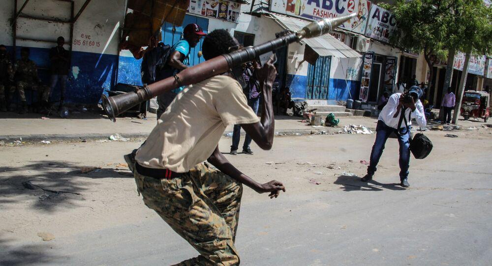 شخص يلتقط صورة لعضو في القوة العسكرية الصومالية يدعم المناوئين للحكومة أثناء وقوفه في أحد شوارع مقديشو، الصومال، 25 أبريل 2021