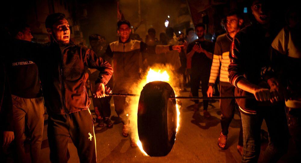 فلسطينيون يحرقون إطارًا مرددين إشعارات مؤيدة للمسجد الأقصى خلال تجمع حاشد في مدينة غزة، قطاع غزة، فلسطين 24 أبريل 2021.