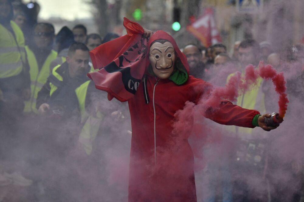 متظاهر يرتدي قناع سلفادور دالي، المستوحاة من المسلسل الإسباني الشهير لا كاسا دي بابيل ( بيت من ورق وبيت المال)، خلال احتجاجات في مارسيليا، فرنسا 14 يناير 2021