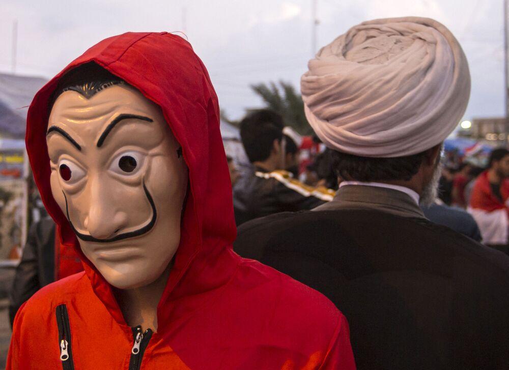 متظاهر يرتدي قناع سلفادور دالي، المستوحاة من المسلسل الإسباني الشهير لا كاسا دي بابيل ( بيت من ورق وبيت المال)، خلال مظاهرات مناهضة للحكومة في البصرة، العراق 29 نوفمبر 2019