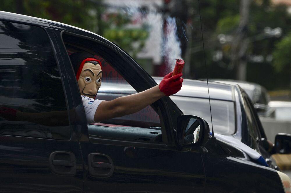 متظاهر يرتدي قناع سلفادور دالي، المستوحاة من المسلسل الإسباني الشهير لا كاسا دي بابيل ( بيت من ورق وبيت المال)، يمسك بشعلة حمراء أثناء مرور قافلة من سيارات المتظاهرين المطالبين باستقالة رئيس هندوراس خوان أورلاندو هرنانديز 29 يوليو 2020