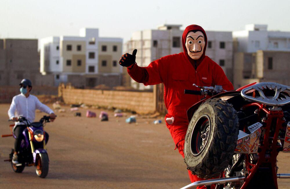 متظاهر ليبي يرتدي قناع سلفادور دالي، المستوحاة من المسلسل الإسباني الشهير لا كاسا دي بابيل ( بيت من ورق وبيت المال)، أثناء أدائه حركات بهلوانية على مركبته في بنغازي، ليبيا 21 أبريل 2021