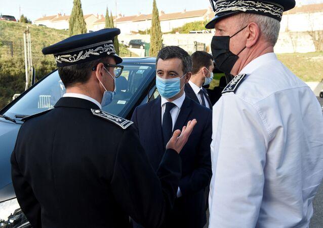 وزير الداخلية الفرنسي جيرالد دارمانين (وسط الصورة) ، يرتدي قناعًا وقائيًا ، يتحدث مع ضباط الشرطة خلال زيارة في مرسيليا ، جنوب فرنسا