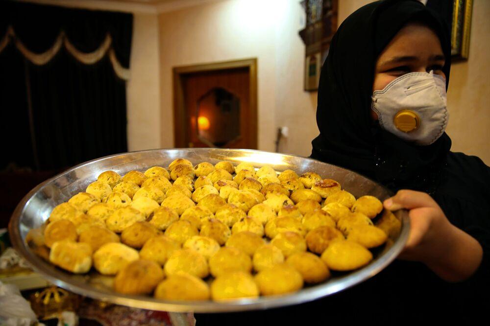 امرأة تحمل صينية معمول عيد الفطر في مدينة البصرة، العراق 13 مايو 2021