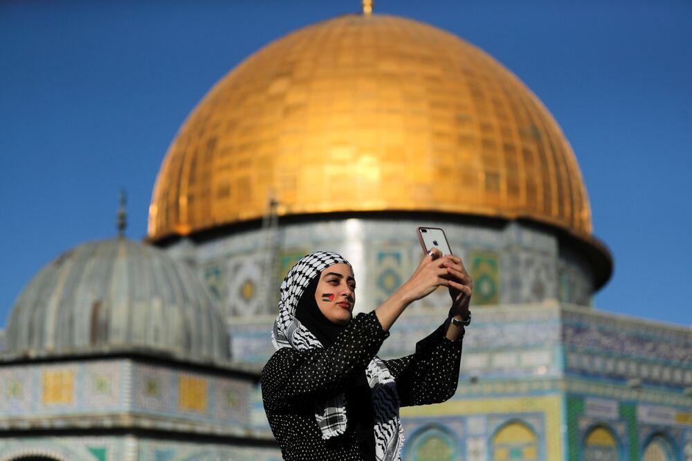 شابة فلسطينية تلتقط صورة سيلفي، بعد صلاة عيد الفطر، على خلفية مسجد قبة الصخرة في باحة مسجد الأقصى، القدس، فلسطين 13 مايو 2021