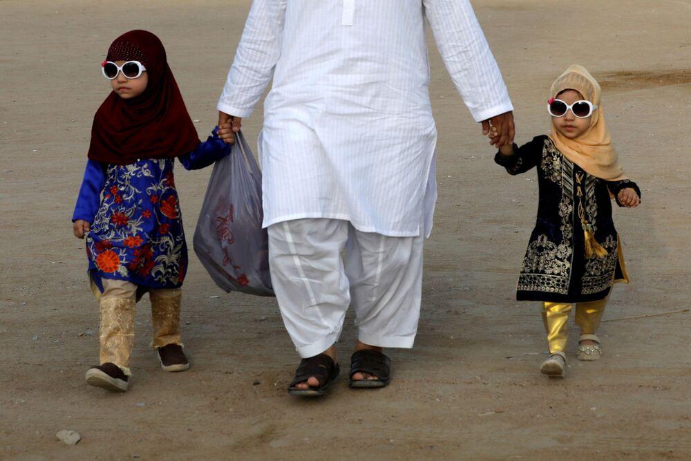 أب مع طفليه بعد صلاة عيد الفطر في مدينة كاراتشي، باكستان 13 مايو 2021