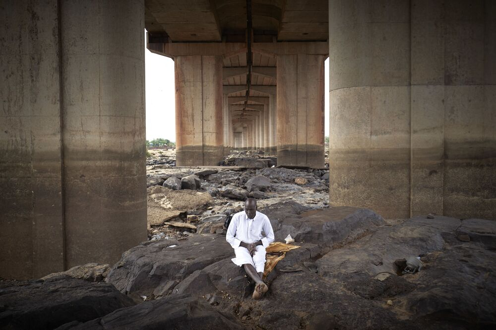 إمام مسجد في سوتادونو يجلس تحت جسر باماكو خلال صلاة عيد الفطر، مالي 12 مايو 2021