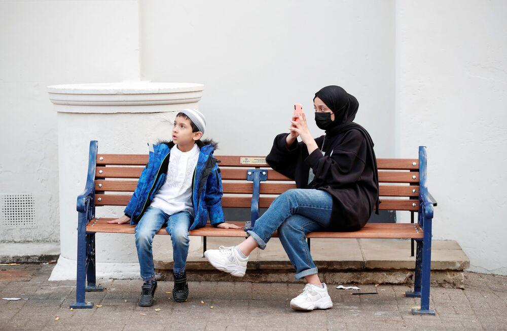 الصبي، موسى خان، والفتاة، تبارك خان، يجلسان قرب مسجد بعد صلاة عيد الفطر في سانت ألبانز، بريطانيا 11 مايو 2021