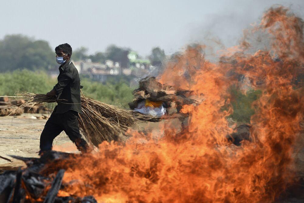 عامل يسير بجوار موقع المحرقة لمرضى كوفيد-19، الهند 9 مايو 2021