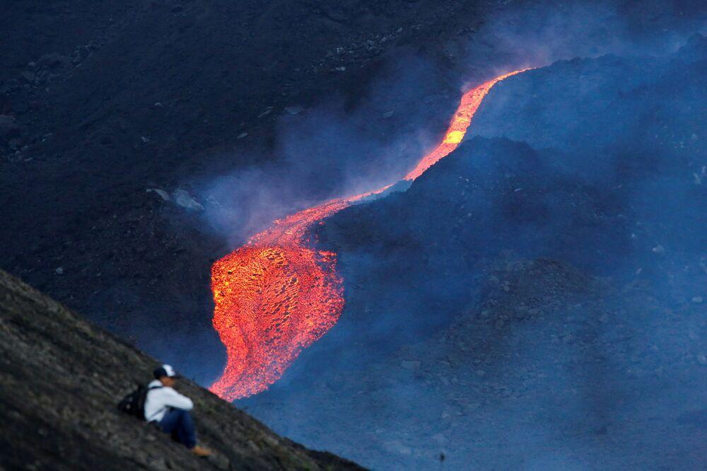 رجل يشاهد تدفق الحمم الساخنة من بركان باكايا في منطقة إسكوينتلا، غواتيمالا 8 مايو 2021