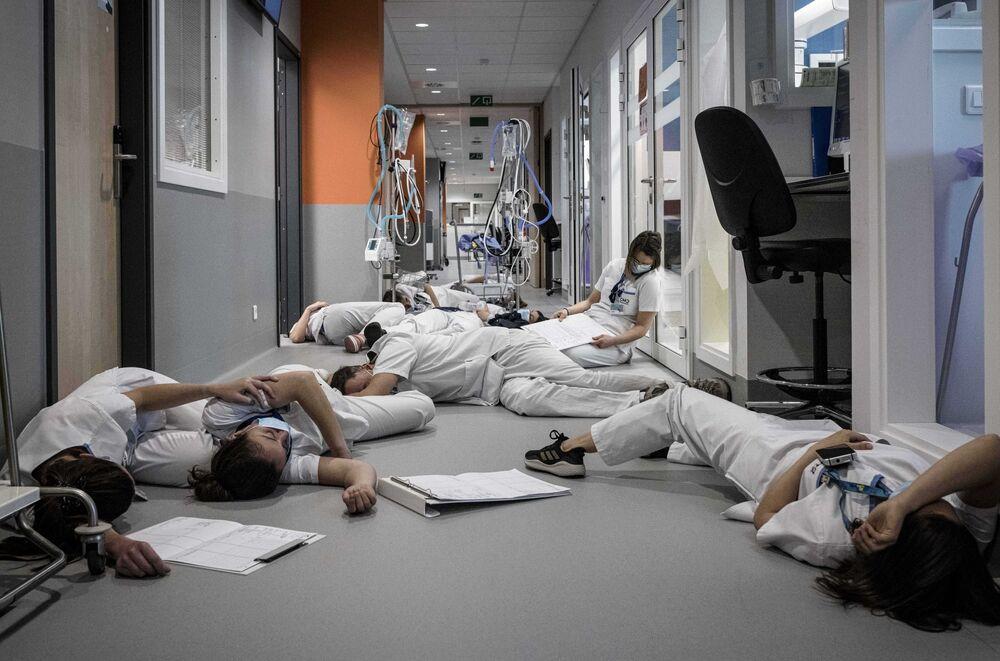 طاقم التمريض ينامون على الأرضية في وحدة العناية المركزة خلال عرض توضيحي في يوم التمريض والعناية الدولي في مستشفى مونت ليجيا في لييج، بلجيكا 12 مايو 2021