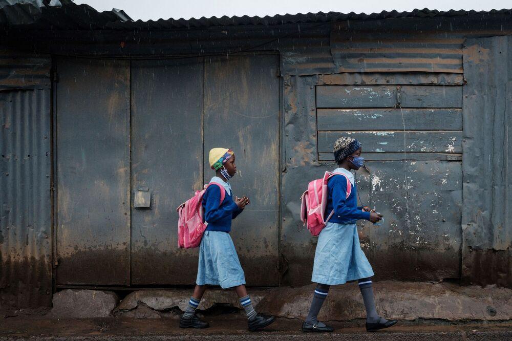 طالبات يذهبن إلى المدرسة الابتدائية الأولمبية مع إعادة فتح المدارس بعد 6 أسابيع من الراحة بتوجيهات من الرئيس الكيني أوهورو كينياتا في إطار الحد من انتشار فيروس كورونا، في حي كيبيرا الفقير، نيروبي، 10 مايو 2021.