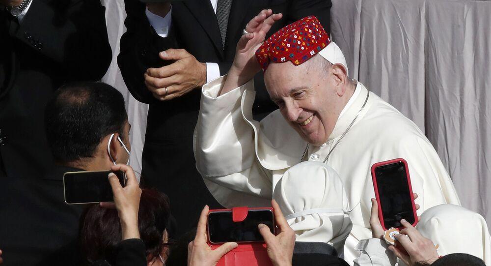 بابا الفاتيكان فرانسيس يبتسم بعد أن وضع أحد الحضور قبعة على رأسه في ساحة القديس داماسو بالفاتيكان أمام جمهوره الأسبوعي، 12 مايو 2021.