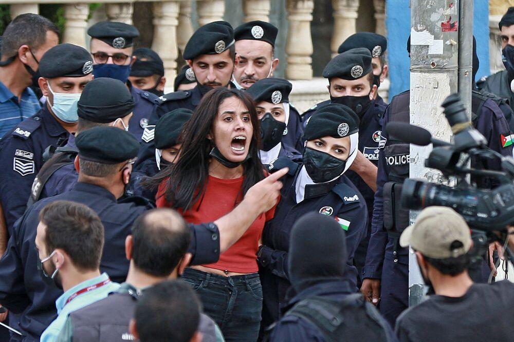 عناصر الشرطة يوقفون متظاهرة خلال مظاهرة تضامنية مع الشعب الفلسطيني بالقرب من السفارة الإسرائيلية في العاصمة الأردنية عمان، الأردن 9 مايو 2021