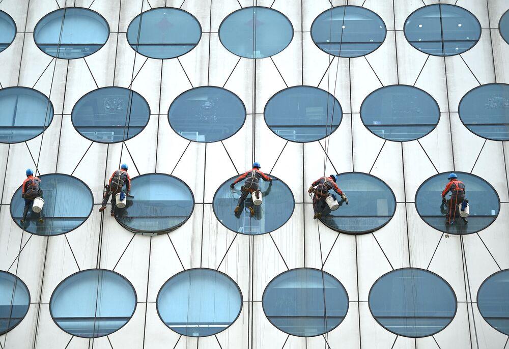 عمال ينظفون نوافذ أحد المباني في بكين في الصين 12 مايو 2021