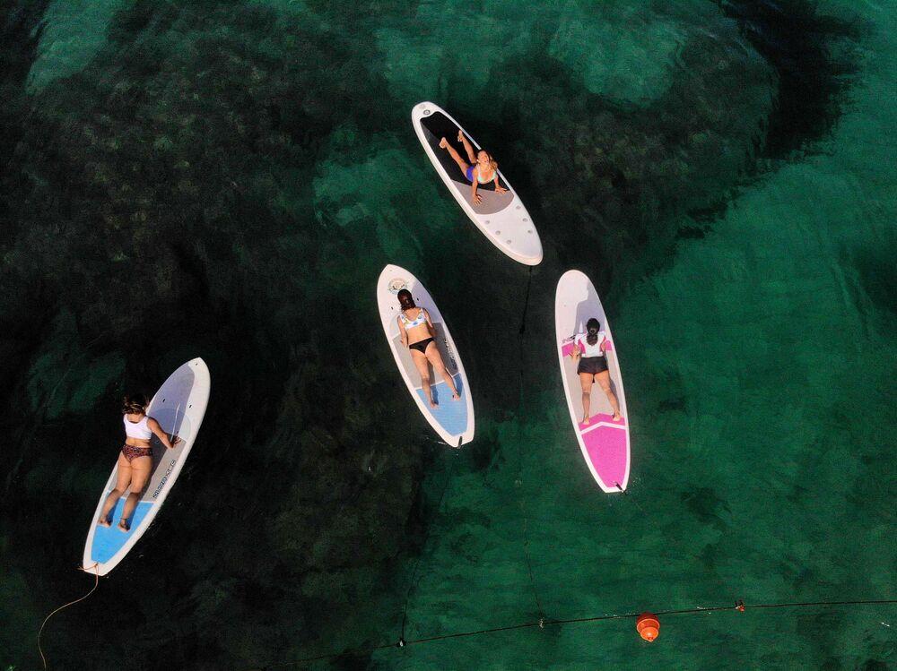 لبنانيات يمارسن اليوغا على ألواح التجديف في البحر الأبيض المتوسط قبالة سواحل مدينة البترون الشمالية، لبنان 8 مايو 2021