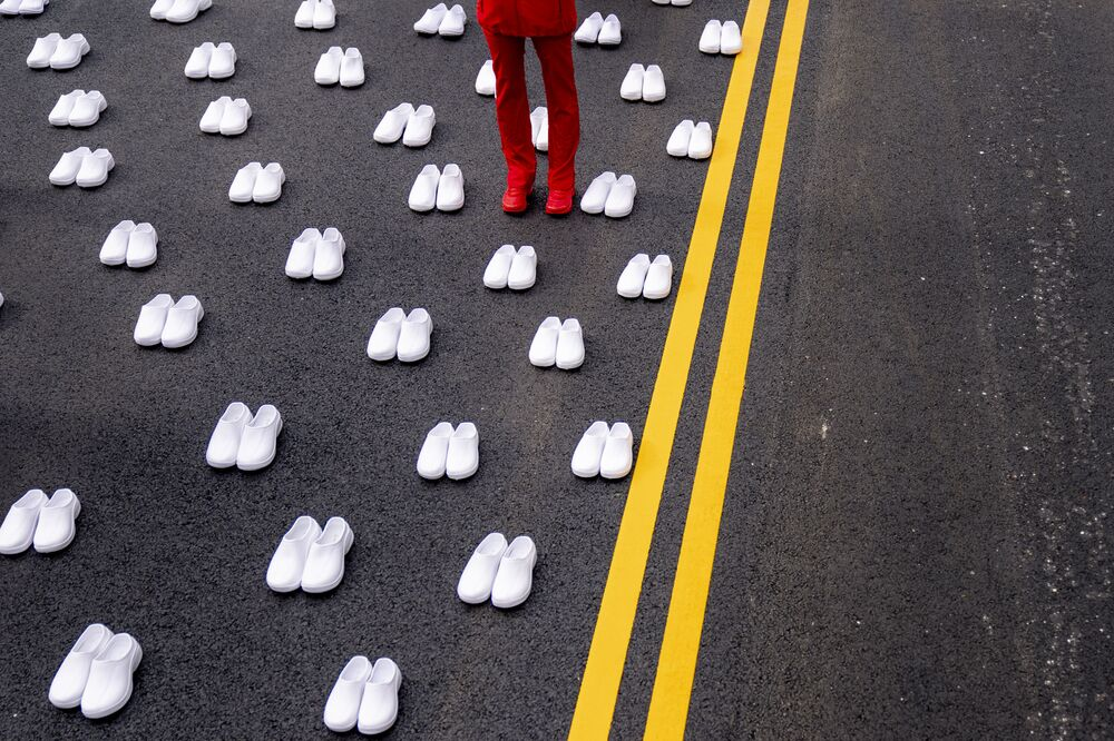 امرأة ترتدي زي الممرضات تقف محاطة بأزواج من الأحذية البيضاء لتمثيل 402 ممرضة توفيت بسبب كوفيد -19، بالقرب من البيت الأبيض في واشنطن، 12 مايو 2021.