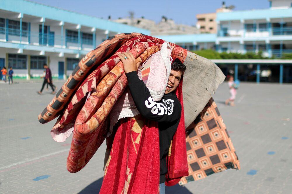 فلسطينيون يغادرون منازلهم عقب اشتداد قصف المدافع والطيران الحربي الإسرائيلي في شمال قطاع غزة ويلجأون إلى مدارس الأونروا، فلسطين 14 مايو 2021