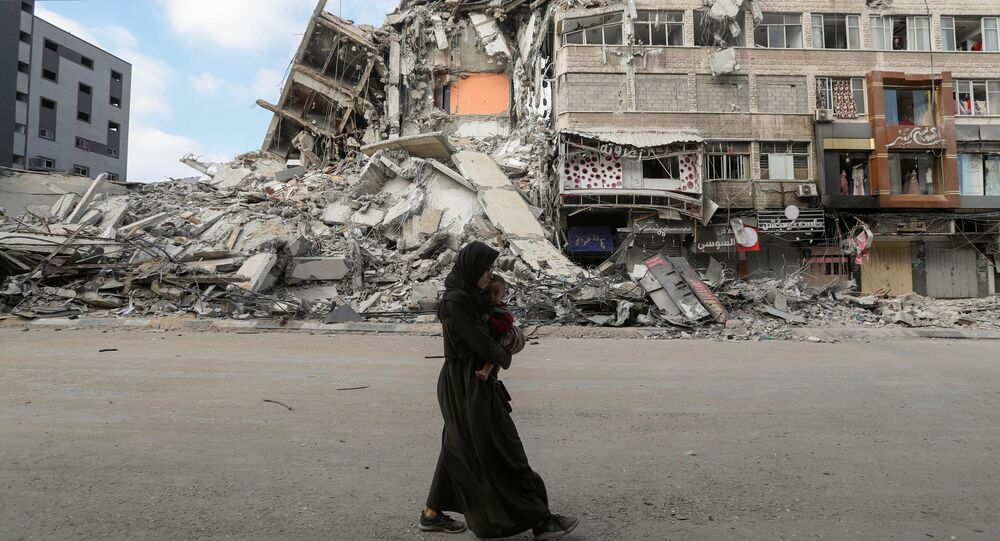 امرأة تحمل طفلها تسير على خلفية ركام منازل، تخلو حييها بعد اشتداد قصف المدافع والطيران الحربي الإسرائيلي في شمال قطاع غزة، فلسطين 14 مايو 2021