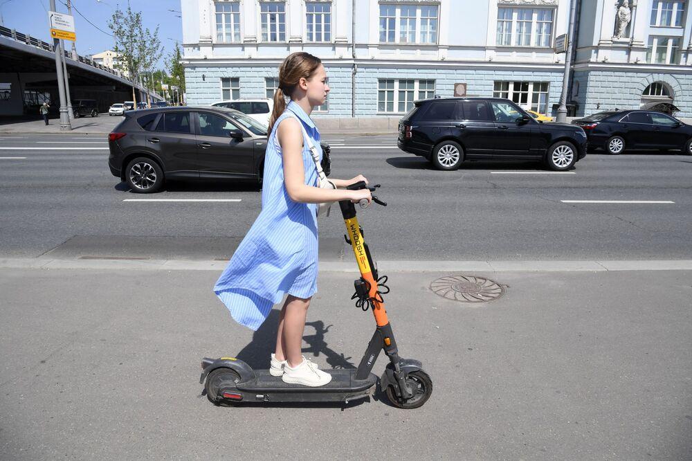 فتاة تركب سكوتر آلي في شارع أستوجينكا وسط مدينة موسكو، روسيا 17 مايو 2021