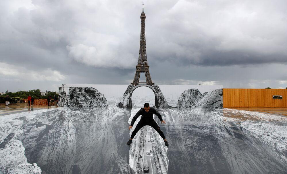 رجل خلال التقاط صورة له، يقف على عمل فني عملاق للفنان الفرنسي جي آر (JR ) مثبت في ميدان تروكاديرو أمام برج إيفل في باريس، فرنسا ، 19 مايو 2021