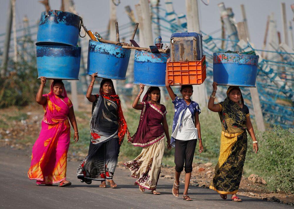 نساء يحملن متعلقاتهن بعد إنقاذهن من أماكن عملهن المتضررة في ميناء صيد بعد إعصار تاوكتاي في جافراباد في ولاية غوجارات الغربية، الهند، 19 مايو 2021