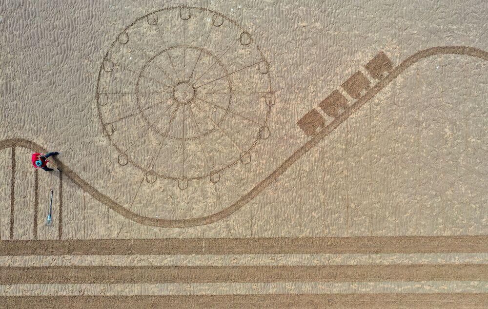 تُظهر الصورة الجوية لوحة رملية تصور البرج الرمزي والرصيف ومناطق الجذب في بلاكبول في شمال غرب إنجلترا، وقد رسمهتها مجموعة من فناني الرمال تسمى رمل في عينك على الشاطئ كعلامة على إعادة افتتاح المدينة بعد تخفيف القيود المفروضة على الدخول إلى إنجلترا بسبب فيروس كورونا، 17 مايو 2021