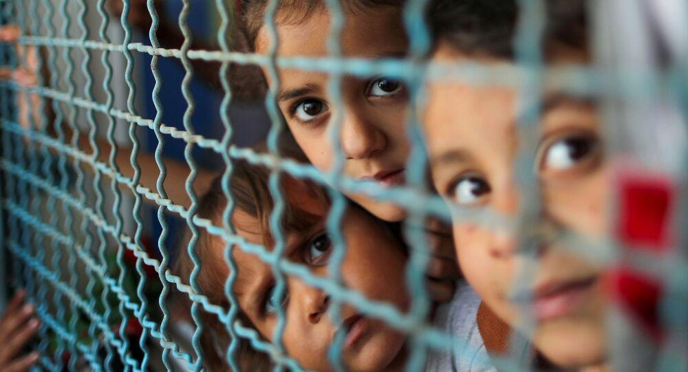 أطفال ينظرون من نافذة مدرسة الأنروا. يذكر أنه نزح ما يقرب 34 ألف من أهالي قطاع غزة إلى مدراس الأونروا بعد قصف الطيران الحربي الإسرائيلي منازلهم، فلسطين بتاريخ 18 مايو 2021