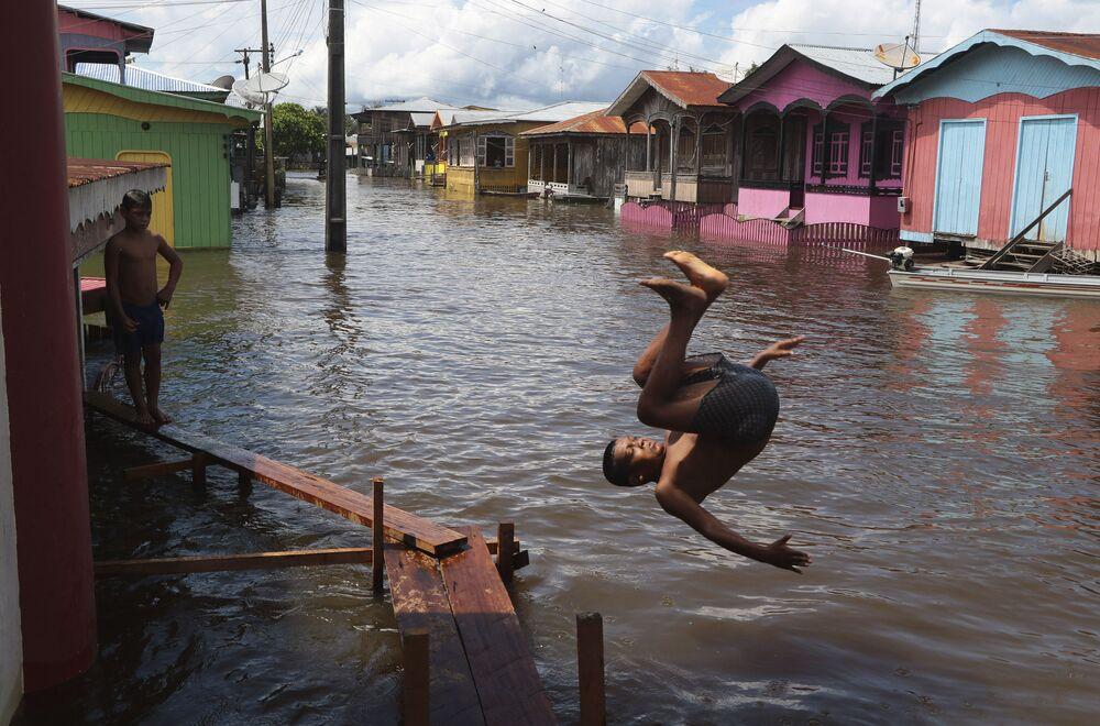 صبي يقفز في شارع غمرته المياه في أناما، ولاية أمازوناس، البرازيل، 14 مايو 2021.