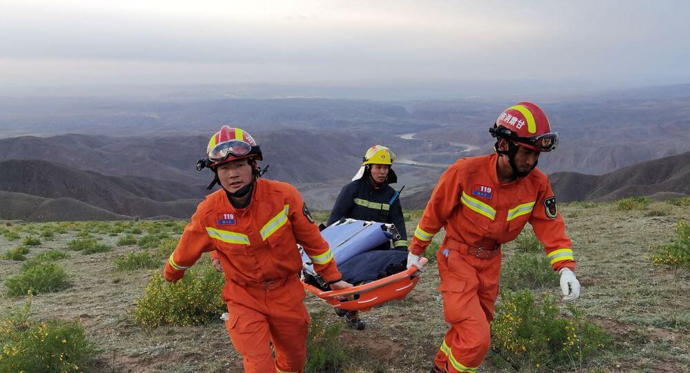 عمال الإنقاذ يحملون نقالة أثناء عملهم في الموقع حيث قتل الطقس شديد البرودة المشاركين في سباق ألتراماراثون بطول 100 كيلومتر في بايين، مقاطعة قانسو، الصين، 22 مايو/ أيار 2021