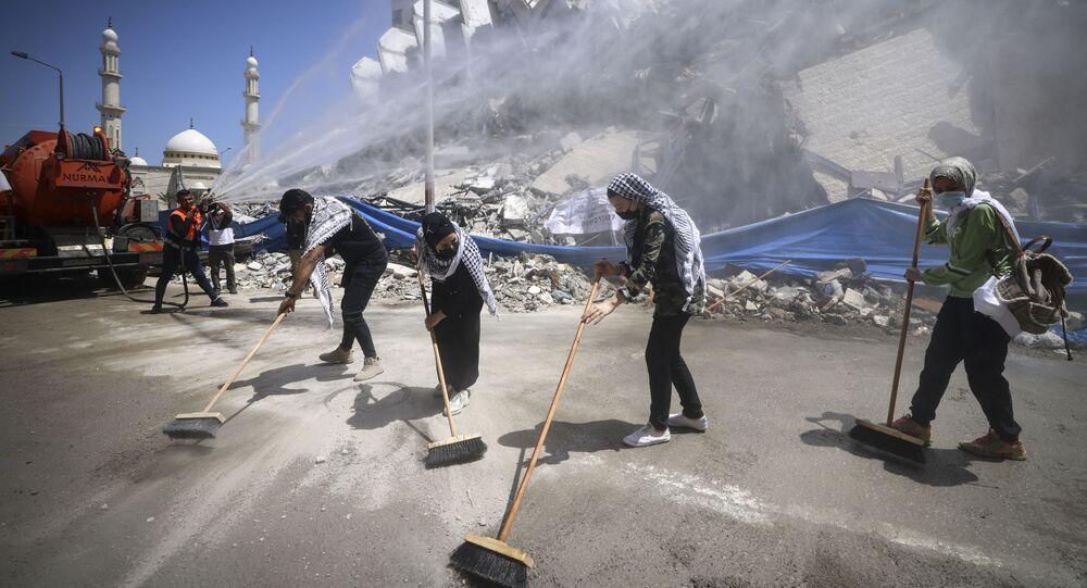 متطوعون فلسطينيون وعمال بلدية يقومون بإزالة أنقاض مجمع برج هنادي، الذي دمرته الغارات الإسرائيلية في الحرب الأخيرة، في حي الرمال بمدينة غزة، في 25 مايو 2021