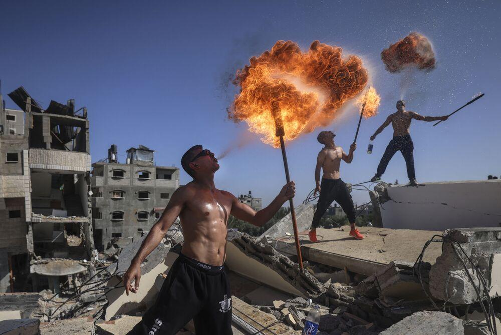 أعضاء فريق بار وولف الفلسطيني من غزة يؤدون عرضًا ناريًا على أنقاض مبنى دمرته الغارات الجوية الإسرائيلية، 26 مايو 2021