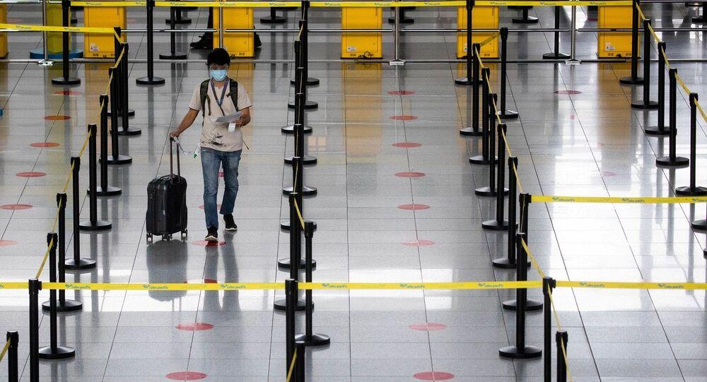 راكب يرتدي كمامة طبية ودرعا للوجه للحماية من فيروس كورونا (كوفيد -19) يسير باتجاه منضدة في مطار نينوي أكينو الدولي في باراناكي، مترو مانيلا، الفلبين، 14 يناير/ كانون الثاني 2021