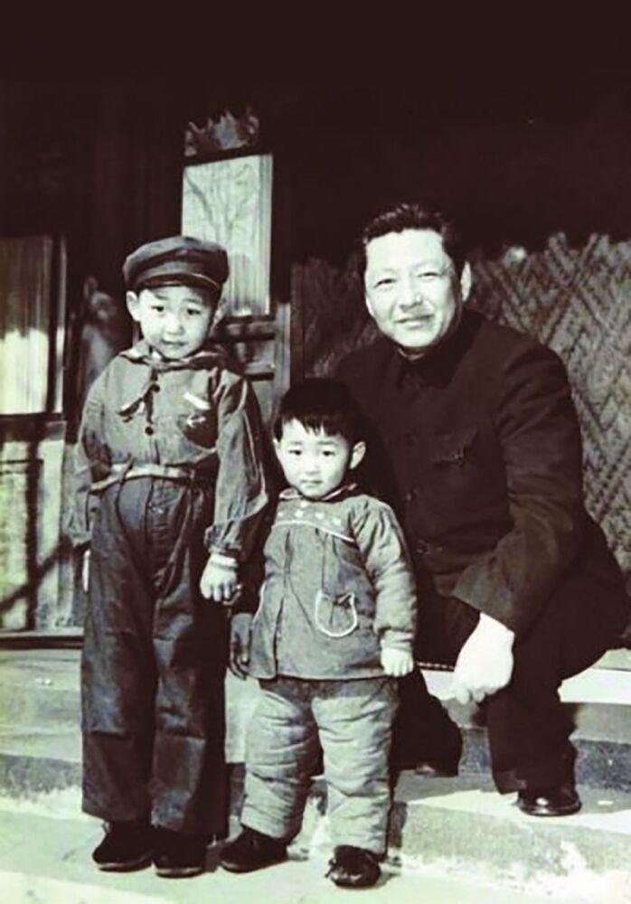 الأمين العام للجنة المركزية للحزب الشيوعي الصيني شي جين بينغ (مواليد 1953) مع والده شي جونغ خون (مواليد 1913) على يسار الصورة، وأخوه يان بينغ (مواليد 1956) على يمين الصورة، وهو الرئيس الحالي للجمعية الدولية للحفاظ على الطاقة وحماية البيئة، عام 1958