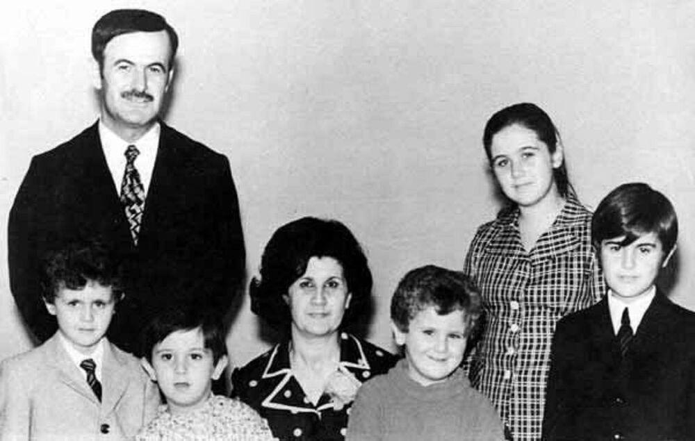 من اليسار إلى اليمين: الرئيس السوري الحالي بشار الأسد (موالد عام 1965)، برفقة والده حافظ الأسد، ووالدته أنيسة مخلوف، وأخوته: ماهر، مجد، بشرى، وباسل، أوائل السبعينات.