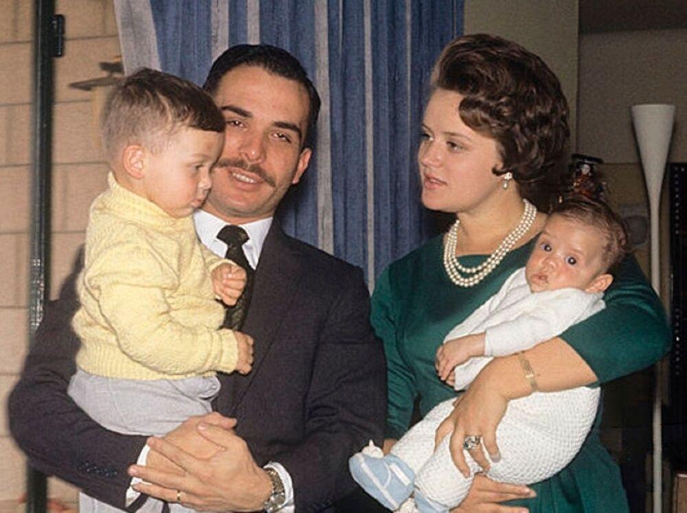 ملك الأردن السابق حسين وزوجته الأميرة منى مع طفليهما الأمير عبدالله الثاني (ملك الأردن الحالي، يسار الصورة)، والأمير فيصل (يمين الصورة)، عام 1964