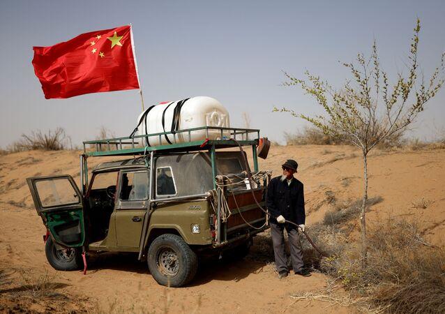 وانغ تيانتشانغ، 78 عامًا، يسقي شجرة مزروعة على حافة صحراء غوبي في ضواحي وووي، مقاطعة غانسو، الصين، 15 أبريل 2021