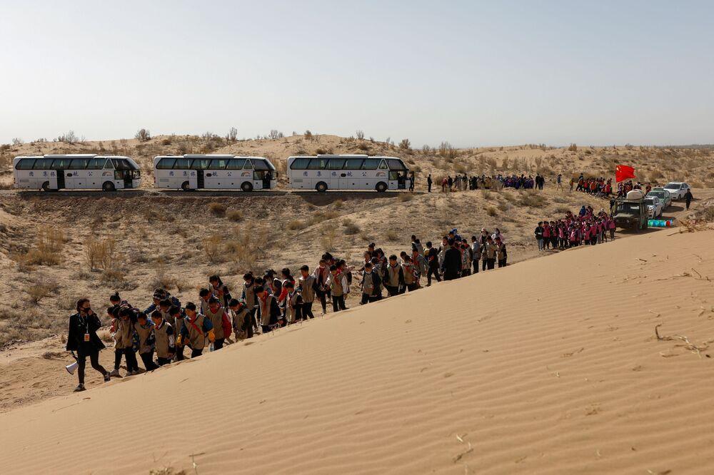 أطفال يسيرون على طول الكثبان الرملية أثناء فعالية لزرع طوعي للأشجار نظمته مدرستهم على حافة صحراء غوبي في ضواحي ووي، مقاطعة غانسو، الصين 16 أبريل 2021