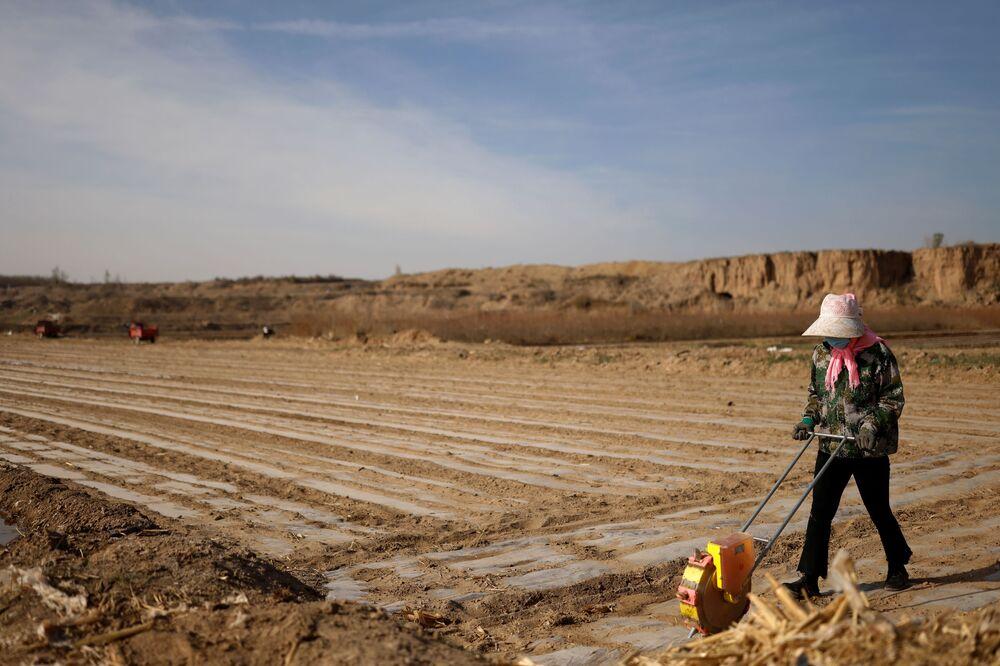 عامل يستخدم زارعًا لزرع بذور الذرة على أرض وانغ ينجي في قرية بالقرب من حافة صحراء غوبي على مشارف وووي، مقاطعة غانسو، الصين، 14 أبريل 2021