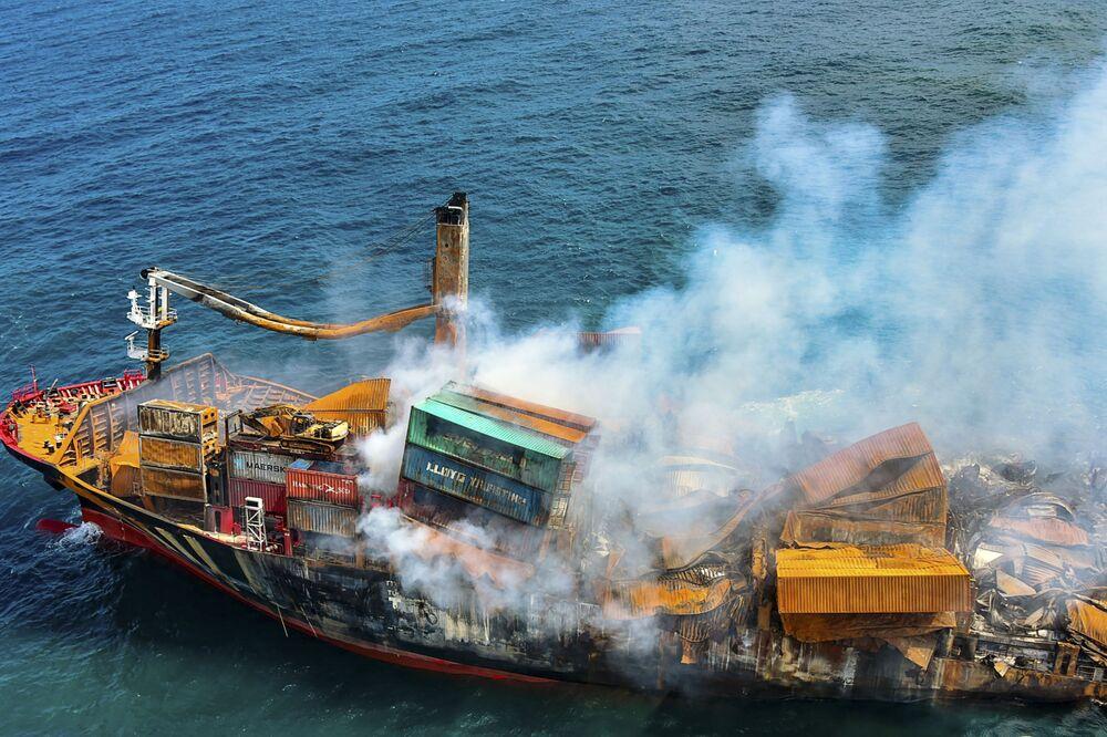 تُظهر هذه الصورة المنشورة التي التقطتها القوات الجوية السريلانكية ونشرتها في 2 يونيو 2021 دخانًا يتصاعد من سفينة الحاويات المسجلة في سنغافورة MV X-Press Pearl، التي تحمل مئات الحاويات من المواد الكيميائية والبلاستيك، أثناء سحبها بعيدًا عن ساحل كولومبو، عقب أمر الرئيس السريلانكي غوتابايا راغاباكسا بنقل السفينة إلى المياه العميقة لمنع كارثة بيئية أكبر.