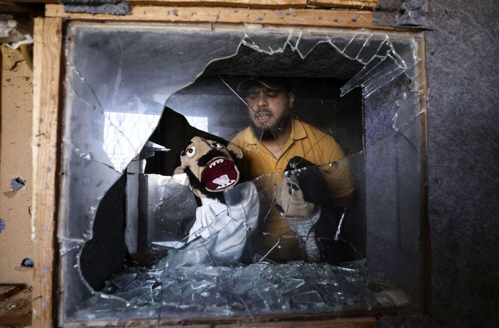 محمد سعيد، فنان كوميدي فلسطيني وشريك الفنان نبيل الخطيب، مؤسس بيت الفن في مدينة غزة، يعرض الدمى التي انتشلها من الاستوديو الخاص بهم، الذي تضرر خلال القصف الإسرائيلي الأخير، 29 مايو 2021، بعد أكثر من أسبوع من وقف إطلاق النار الذي أنهى 11 يومًا من الأعمال العدائية بين إسرائيل وفصائل المقاومة الفلسطينية في قطاع غزة.
