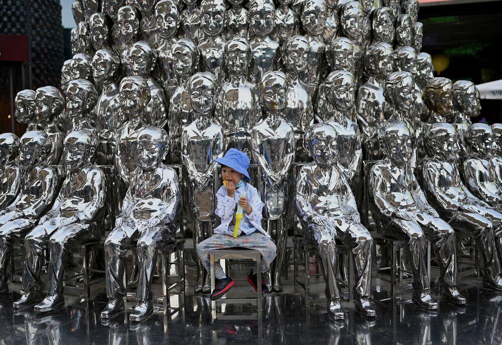 صبي يجلس على كرسي بين منحوتات معروضة في مركز تسوق في يوم الطفل العالمي في بكين في الأول من يونيو 2021، بعد يوم من إعلان الصين بالسماح للأزواج بإنجاب ثلاثة أطفال.