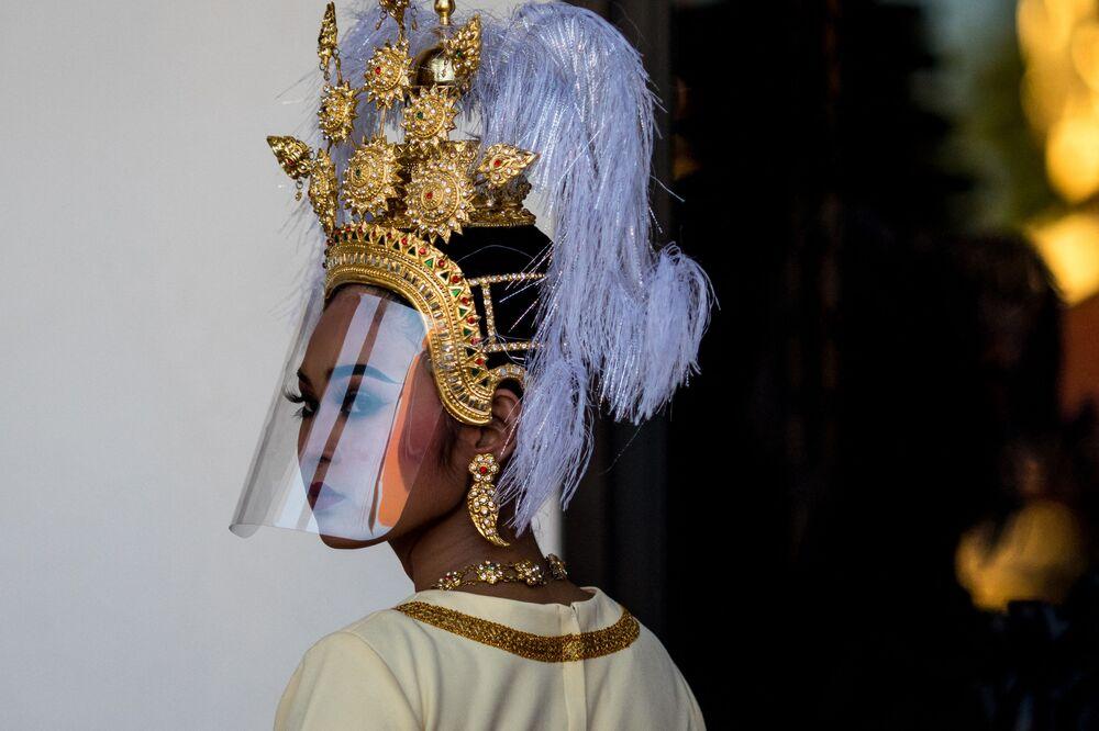 راقصة تايلندية تقليدية ترتدي قناعاً واقياً، استعداداً للمراسم الاحتفالية بمناسبة عودة اثنين من عتبات الحجر الرملي القديم ، وهي عوارض دعم مقدسة من الحجر الرملي من أواخر القرن العاشر أو الحادي عشر، في متحف بانكوك الوطني في بانكوك في 31 مايو 2021